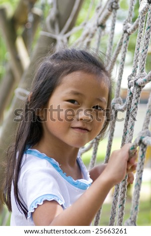A young Asian Girl playing on a Rope ladder in a playground.