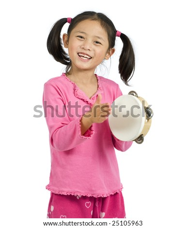 A young asian girl playing Tambourine - stock photo