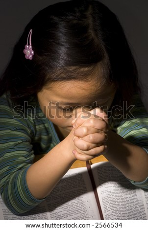 A young Asian girl praying on a bible - stock photo