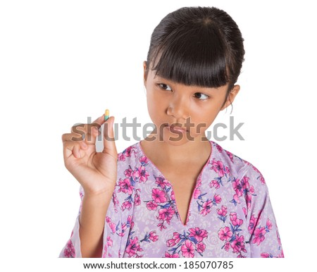 A young Asian girl with face expression with tablet medicine for health care over white background