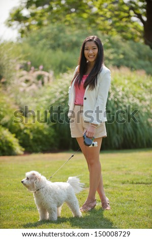 A young Asian girl with her dog at a park  - stock photo