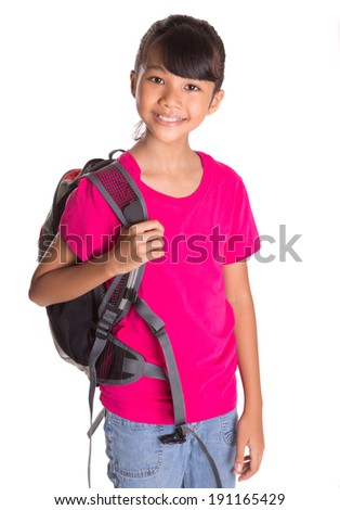 A young Asian Malay girl with a backpack over white background - stock photo