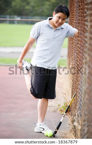 A young Asian male stretching before playing tennis - stock photo