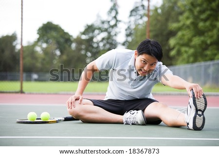 A young Asian male tennis player stretching before playing - stock photo