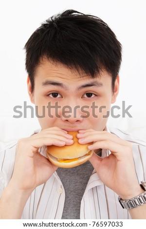 A young Asian man biting into a burger - stock photo