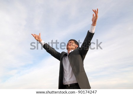 A young Asian man in suit smiling, raised his hands up. He is pleased. - stock photo
