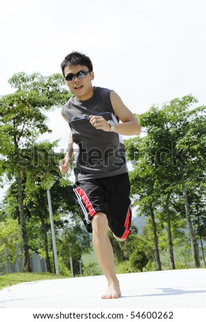 A young Asian man jogging barefoot at a public park - stock photo