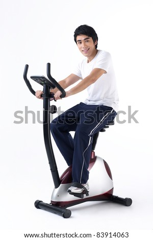 A young asian man training on exercise bicycle - stock photo