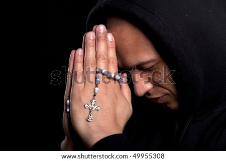 A young asian man with a hoddie is praying over black - stock photo