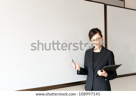 a young asian teacher teaching in the classroom - stock photo