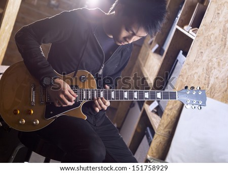 A young asian teenager playing electric guitar with a spotlight shining from the back. - stock photo