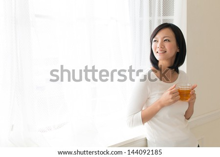 a young asian woman drinking in the room - stock photo