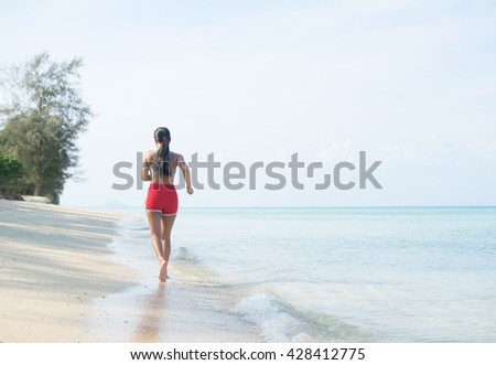 A young Asian woman exercises, running along a tropical beach, back view. Fitness and vacations.