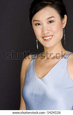 A young asian woman in a baby blue satin dress
