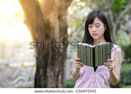 A young asian woman is reading a book
