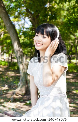 a young asian woman listening music in the park - stock photo