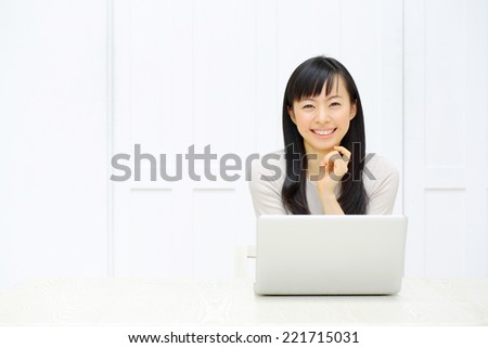 a young asian woman using laptop in the dining room - stock photo