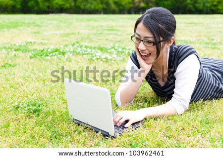 a young asian woman using laptop in the park