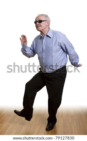 A young at heart senior man dancing alone, isolated on white. - stock photo