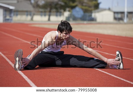 A young athlete doing a warm up leg stretch before a race. - stock photo