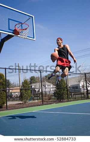 A young athlete flying through the air towards the basketball hoop for a lay up or slam dunk.