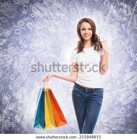 A young, attractive and happy teenage shopping girl with bright shopping bags. Christmas and winter seasonal discounts concept. - stock photo