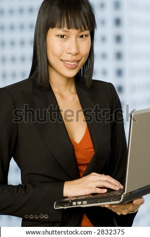 A young attractive asian businesswoman holding a laptop with a building behind her (shallow depth of field used)