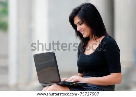 A young attractive Asian businesswoman sitting outside with laptop - stock photo