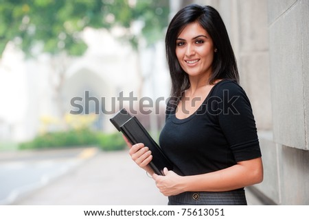 A young attractive Asian businesswoman standing outside - stock photo