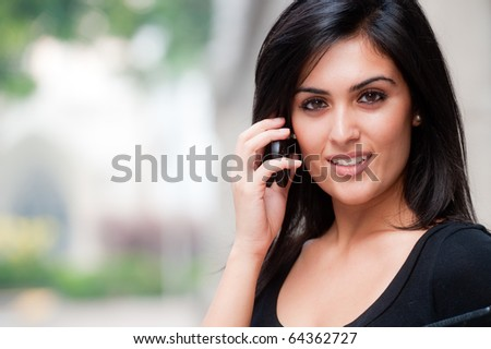 A young attractive Asian businesswoman standing outside with mobile phone - stock photo