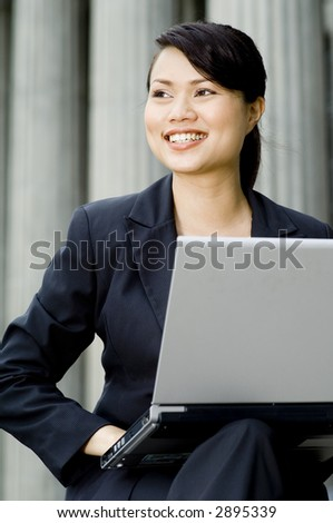 A young attractive asian businesswoman with laptop smiling (shallow depth of field used)