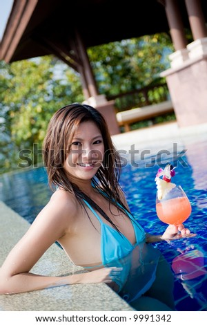 A young attractive Asian woman holding a cocktail in swimming pool - stock photo