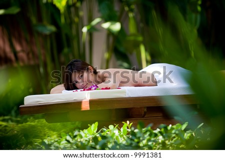 A young attractive Asian woman lying outside ready for a massage
