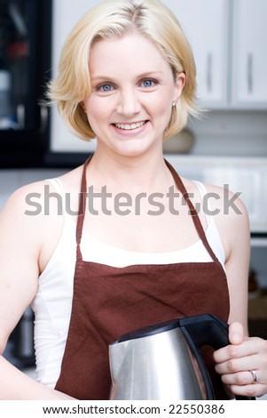 A young attractive blond woman holding a kettle in the kitchen - stock photo