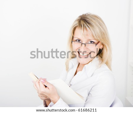 a young attractive blonde with glasses and a book - stock photo