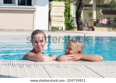 A young attractive blonde woman swimming in a swimming pool with her son