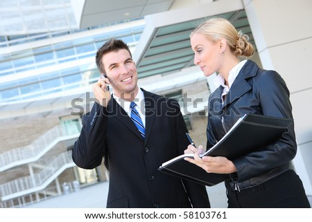 A young attractive business man and woman team at office building - stock photo