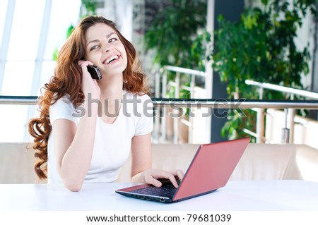 A young attractive business woman sitting in a cafe with a laptop and cell phone - stock photo