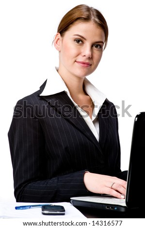 A young attractive businesswoman sitting at a laptop computer - stock photo