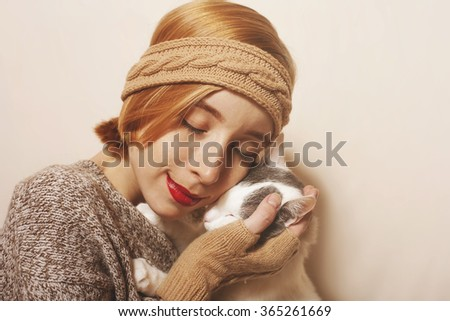 A young, attractive caucasian woman holding a white cat - stock photo