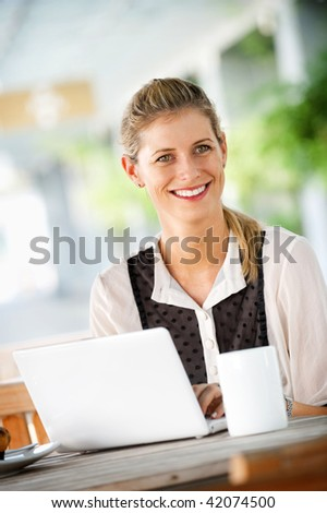 A young attractive caucasian woman uses a laptop outdoors at a cafeteria