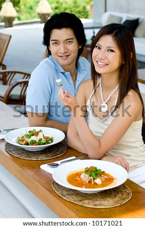 A young attractive couple eating Thai food - stock photo