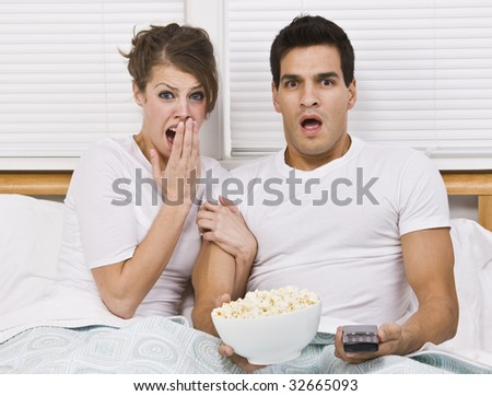A young, attractive couple is sitting together in bed and watching TV.  They look shocked or scared, and are looking away from the camera.  Horizontally framed shot. - stock photo