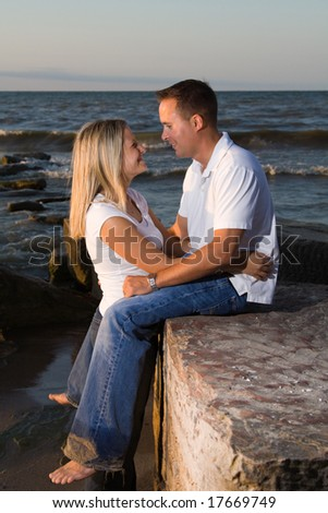 A young attractive couple on the beach at sunset - gaze into each other's eyes.