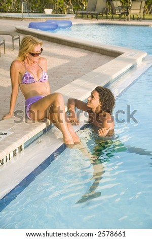 A young attractive couple play flirtatiously at the pool