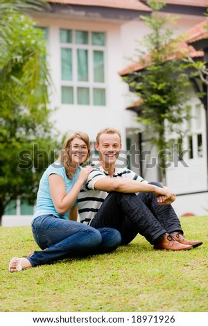 A young attractive couple sitting in garden in front of their house