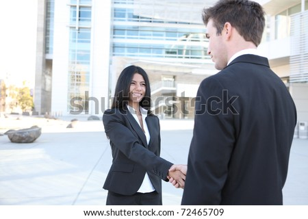 A young attractive diverse man and woman business team handshake at office - stock photo