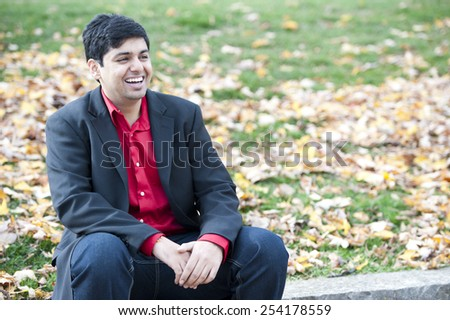 A young attractive Indian man sitting outdoors on a cloudy day in the fall. - stock photo