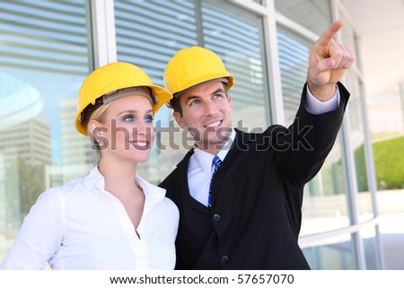 A young attractive man and woman construction team on work site - stock photo