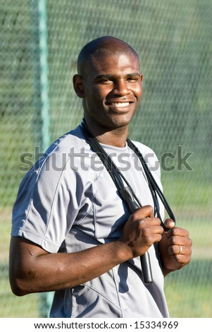 A young, attractive man is standing on the tennis court holding jump ropes around his neck.  He is smiling and looking at the camera.  Vertically framed shot. - stock photo